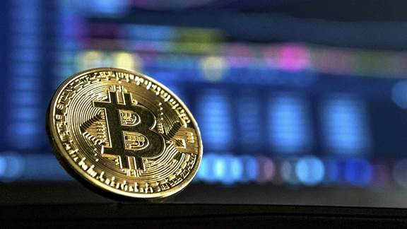 Image of bitcoin with stock market screen behind