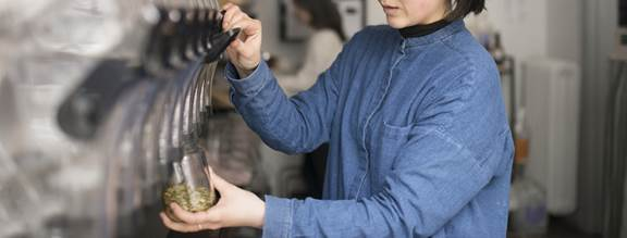 Woman filling reusable container with seeds