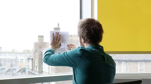 Man holding a piece of paper against a window