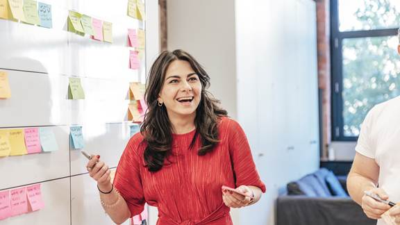 Woman next to a kanban board with sticky notes