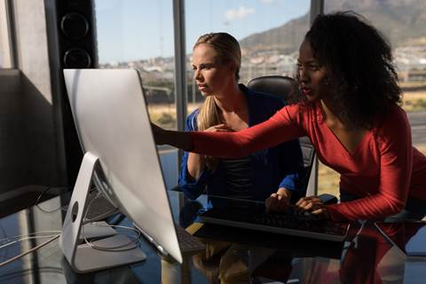 women working together pointing at desktop computer