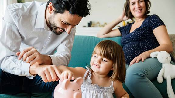 family teaching the baby to save with a low tech pig bank