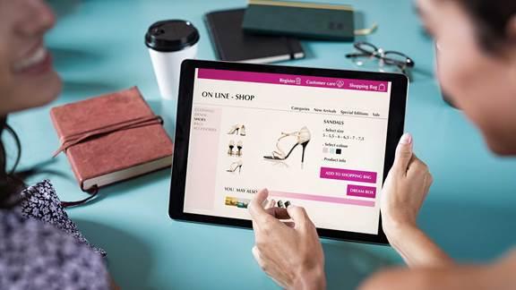 Friends choosing shoes to buy online