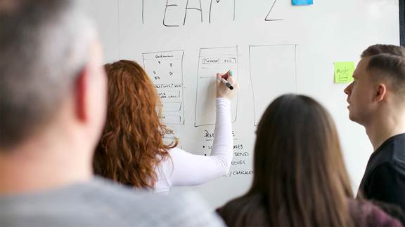 woman writing the software development strategy on a whiteboard