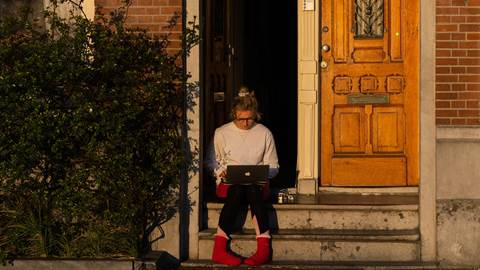 Woman sitting on doorstep with laptop