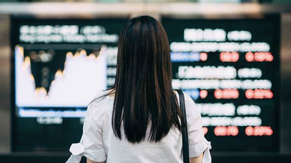 woman looking at a stock exchange screen