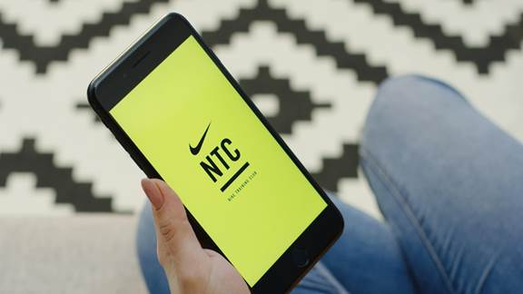 Close up of the female hands opening Nike Training app on the vertical black smartphone