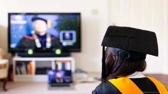 student in graduation gown graduating virtually