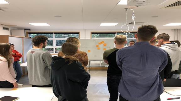 Group of designers looking at whiteboard