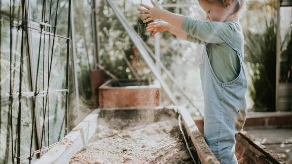 Little girl digging soil in a greenhouse