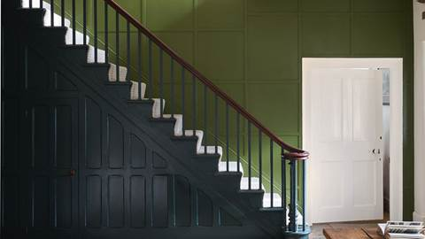 Staircase in a home in farrow and ball dark green paint