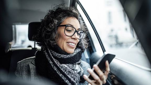 Woman smiling at her phone in the back of a taxi