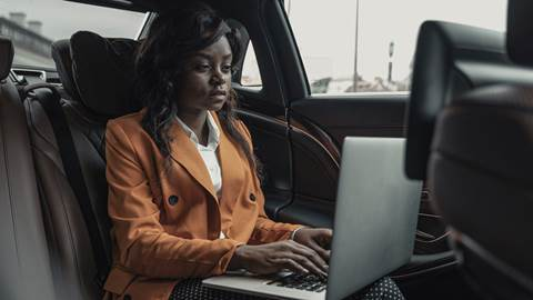 Woman typing on laptop in car
