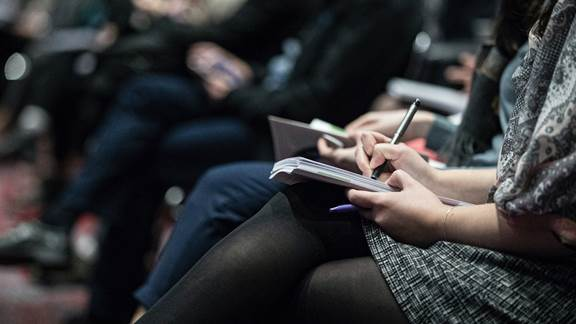 People sitting at conference taking notes