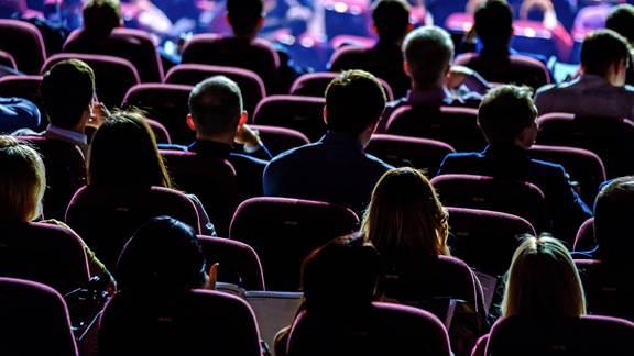 People sat listening to speaker talk in a dark room