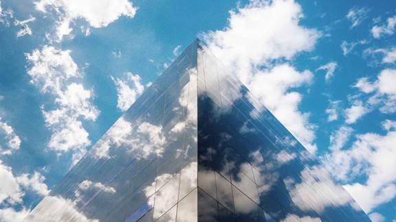 Modern building with cloudy sky reflection