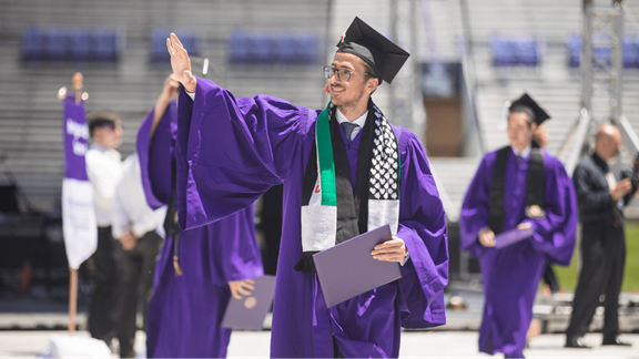 Picture of Omar walking at his college graduation