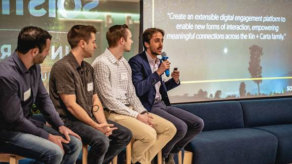 Four employees sitting on a panel, with one employee (Omar) speaking into a microphone