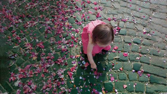 girl playing with roses petals