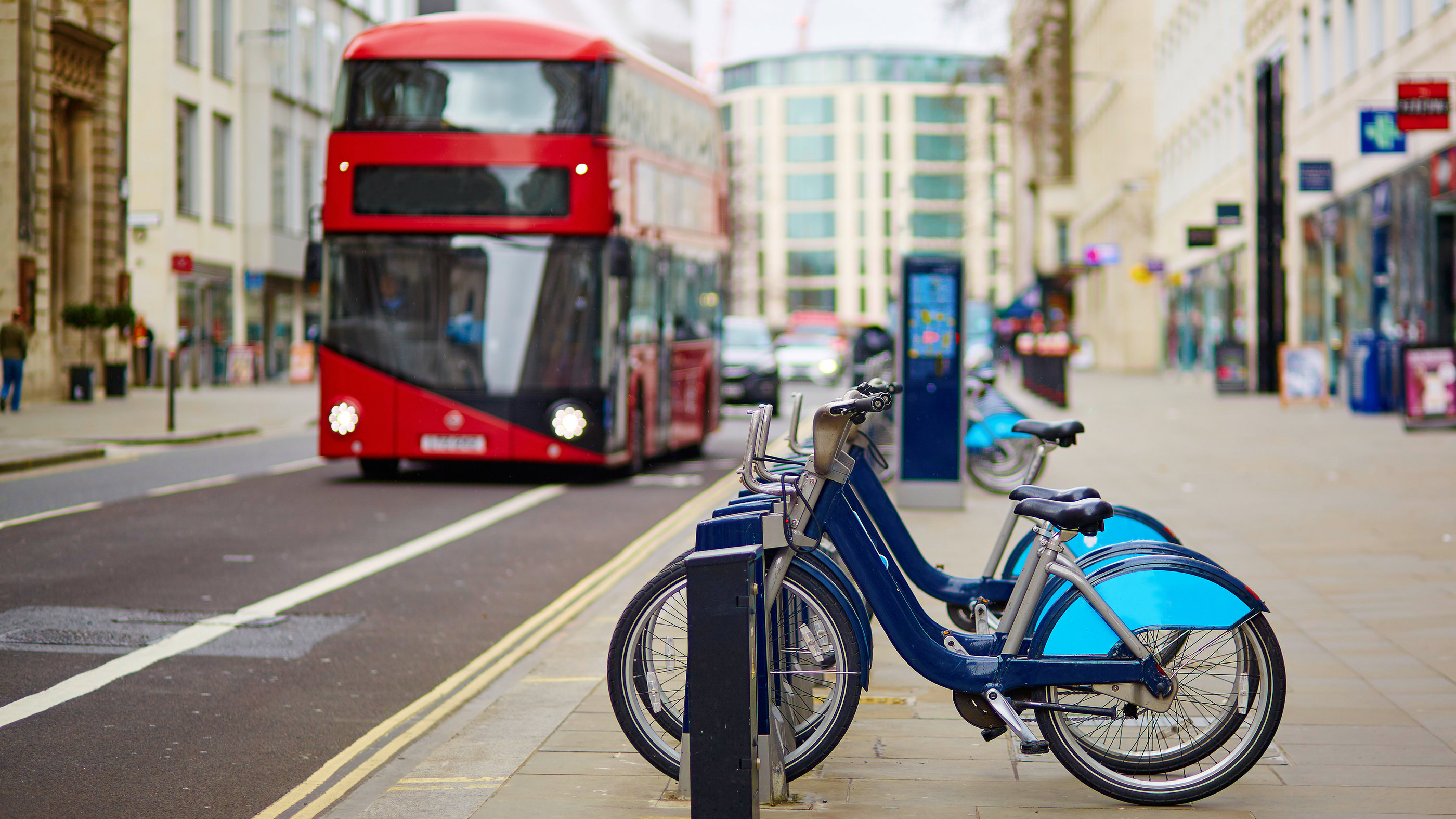 Row of bicycles for rent with red double-decker bus in the background on a street of London, UK