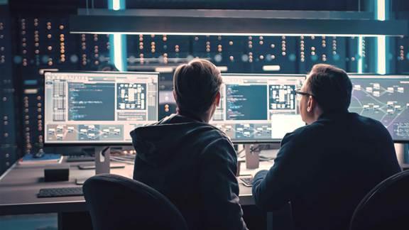 Two men in a server room with desktop screens